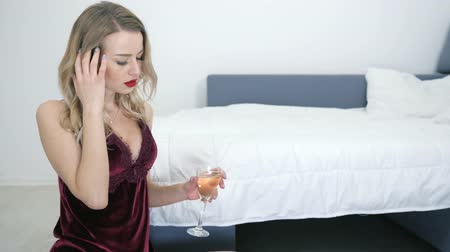 camisola : tired blonde having headache in a sexy nightie holds glass with champagne sitting near bed on floor in room Vídeos