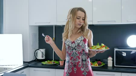 camisola : sexy girl listens to music on headphones and dances with a plate of salad in hands in the kitchen