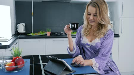 camisola : sexy blonde in a bathrobe uses tablet computer and drinks coffee at a table in the kitchen morning Vídeos