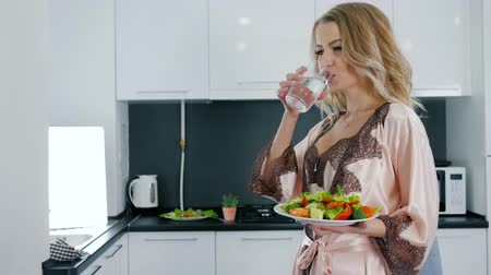 camisola : good morning, happy woman in silk nightdress holds dish with fresh vegetables salad and drinks water from glass