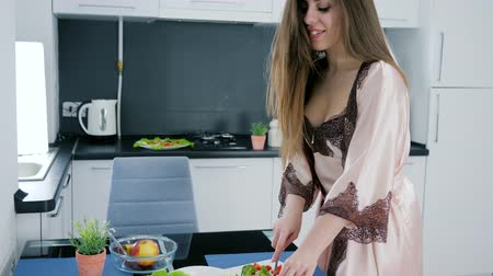 camisola : girl in the morning in a sexy nightgown and bathrobe preparing a salad of vegetables at kitchen Vídeos