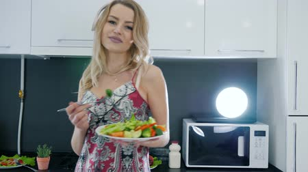 camisola : girl in earphones look at camera and holds plate of vegetable salad with fork at home on kitchen