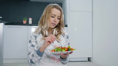 rty : cute girl eating fresh healthy vegetable salad sitting on the floor in pajamas in the kitchen