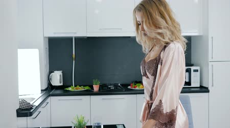 camisola : blonde in silk robe eats vegetables salad and drinks water from glass at modern kitchen in morning Vídeos
