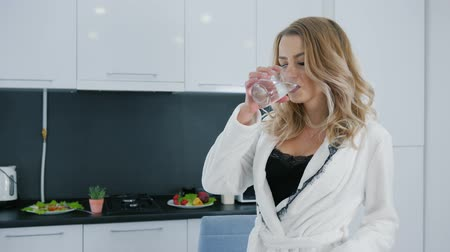 camisola : blonde girl in beautiful pajamas and white robe drinks water from glass in morning at a modern kitchen