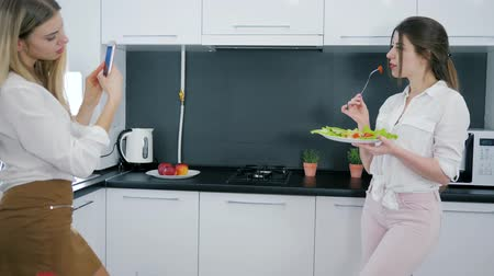 ware : at kitchen girl poses with fork and salad in hands, attractive girlfriends use a smartphone Stock Footage