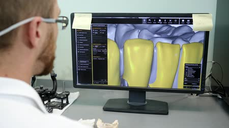 scholar : modern technologies in dentistry, young engineer in 3D glasses looks on model of human teeth on computer at laboratory