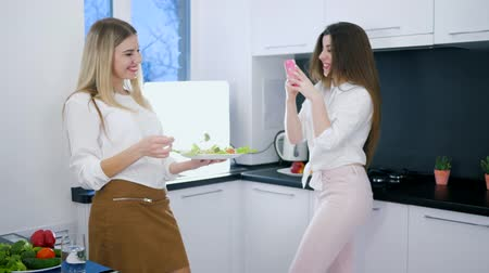 útil : useful food, pleased girls are photographed on telephone standing in kitchen with vegetarian meal in arms Vídeos