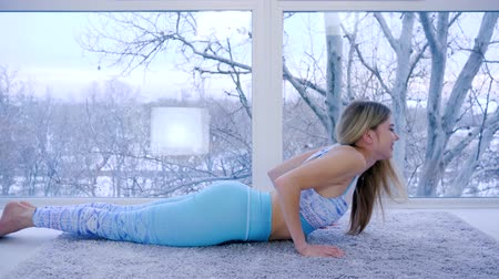 užitečný : fitness of slim girl with elastic body near big window indoors