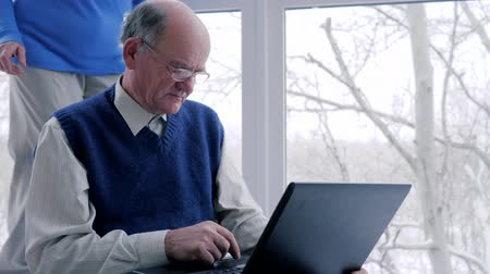 prarodič : older man and woman with laptop spend time on internet on vacation in room near window