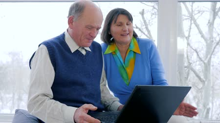 пожилые : payment online modern old people, happy husband and wife talk in skype with computer at home near window