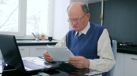throws : grandfather works in internet on computer with documents into hands at home payment online Stock Footage