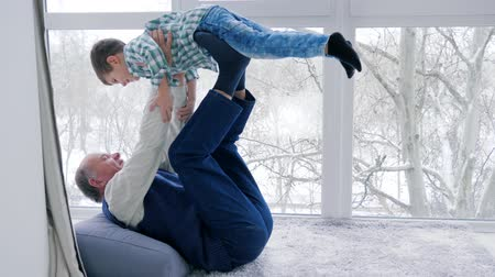 крошечный : grandfather are played with grandson lying on floor indoors near window