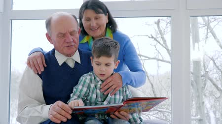 unokája : boy with grandpa and grandma read book and watching pictures at home at leisure