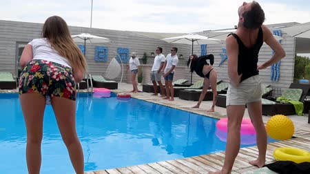 yakın : Azure, Ukraine - 16 August 2017: company of friends barefooted do exercises in slow motion beside blue swimming-pool on background young people in Azure, 16 August 2017.