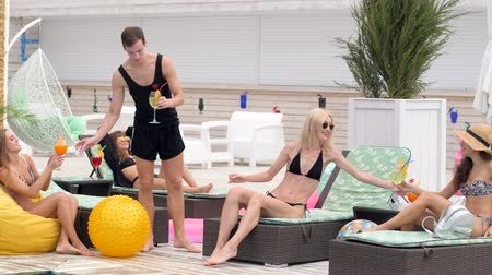przyjaciółki : Cheerful young people in bathing suits enjoy colored drinks and sitting on sun lounger near swimming-pool