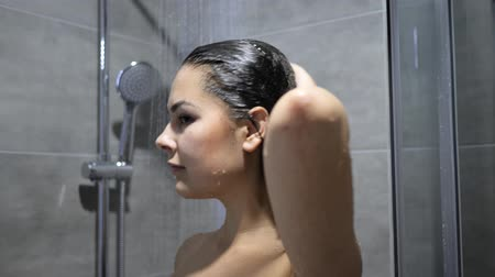 naga : hair care Beautiful brunette pours shampoo on long hair in slow motion under shower in bath room Wideo