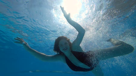 nadador : sexy young woman jumps into blue pool in slow motion and swims with open eyes underwater in vibrant environment on background bubbles summer Stock Footage