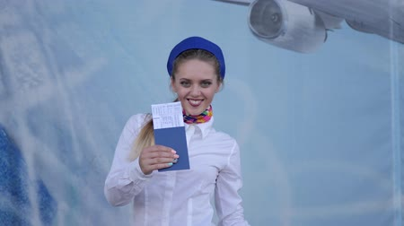 attendant : stewardess holds in hand passport with tickets and shows simbol of approval like on camera at aeroport