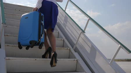 attendant : stewardess in airport holds in hands suitcase and passport with air ticket stands on stairs of plane Stock Footage