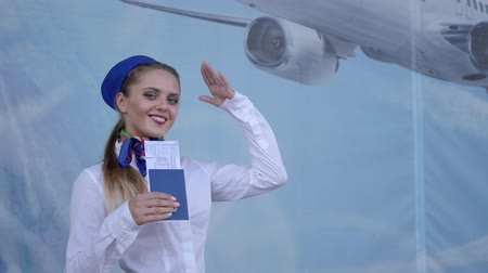 attendant : happy flight attendant holds in hand documents for air travel and salutes at camera on blue background