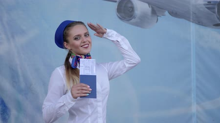 attendant : flight attendant holds in hand passport with tickets and salutes at camera on blue background in aeroport
