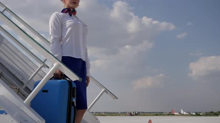 attendant : attractive flight attendant on movable staircase keeps travel bag on background blue sky and looking into distance in aeroport