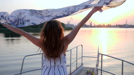 csillogás : Happy Girl waving of attire to wind on Aboard yacht to River on background pink Sunset in slow motion