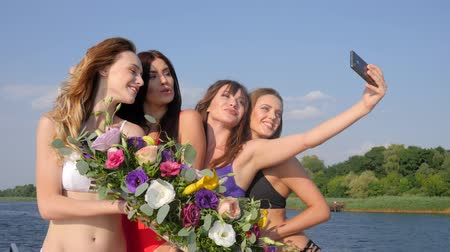 floweret : hen-party Slim Girls In swimsuits with flowers in hands Make selfie On seafront Near from water Stock Footage