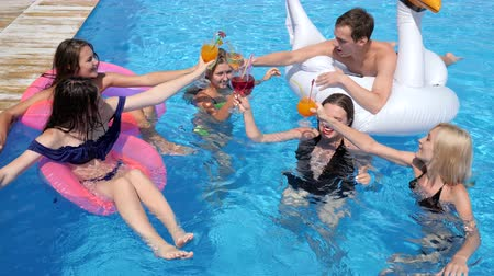 матрац : pool party company of youth on inflatable rings with alcoholic drinks are resting in Poolside at luxurious resort on summer vacations