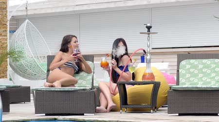 fuma : gossips Beautiful girls In swimsuits smoke hookah and drink cocktails sitting on Pouf near pool on summer rest Vídeos