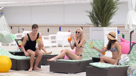 barefooted : group of Happy friends in swimsuits Drink colored cocktails at Summer weekend at resort Stock Footage