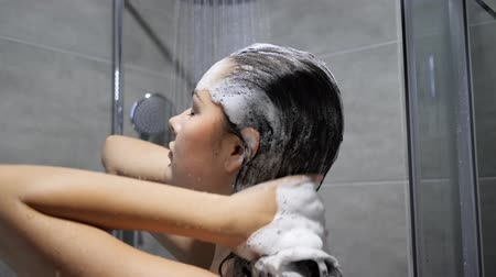 naga : Pretty Young female in lather with pleasure washing hair with shampoo in shower close-up
