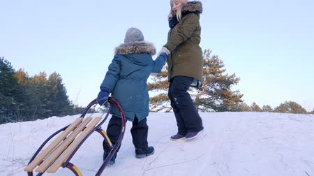 toboggan : winter entertainment, mom and son climb the snow-covered hill with sledges in their hands