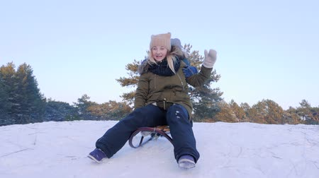 toboggan : winter fun outdoors, mother and son ride on sleigh at snow into the forest in slow motion