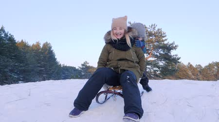toboggan : winter entertainment, happy mother and son ride in a sleigh on snow into the forest in the open air