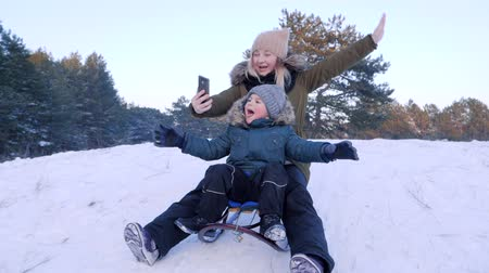 toboggan : mom and son on a sleigh on snowy hill taking pictures of themselves using mobile phone Stock Footage