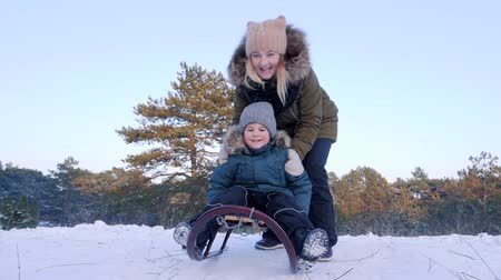 toboggan : in winter forest mother pushes son on sledge and he riding from the snowy hill in slow motion Stock Footage