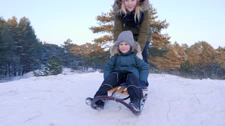 toboggan : happy childhood, mother pushes son on sledge and he riding from the hill in winter forest in slow motion