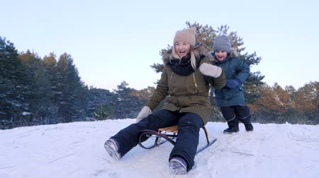 toboggan : family vacation, little boy pushes mother on sledge and she riding from the snowy hill in winter forest in slow motion Stock Footage