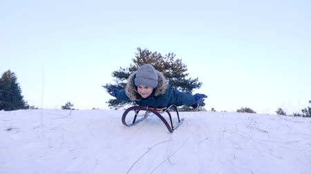toboggan : cheerful boy with raised hands lying on a sled and rides from snowy hill in winter forest in slow motion Stock Footage