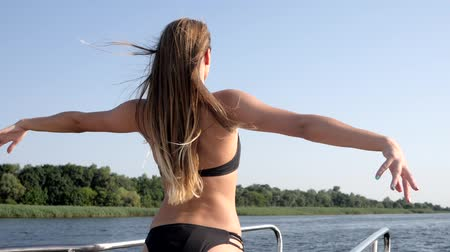 emelt : vacation on yacht, rear view sexy girl in black swimsuit raises hands and enjoys weekend on river in summer season Stock mozgókép