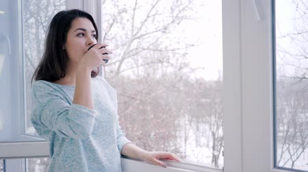 breathing fresh air : enjoying weekend, lovely woman drinks hot coffee standing by open window at home Stock Footage