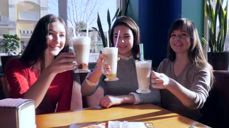 canteen : friends toasting, joyful girls with milkshakes rest in cafe near window on weekends Stock Footage