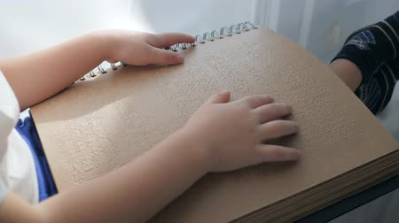impaired : Visually impaired child is reading braille with help of hands close-up