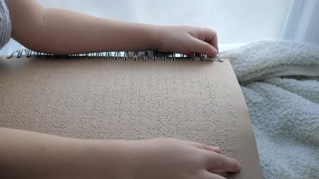 impaired : school of blind, sick child reading braille book touching protuberances close-up