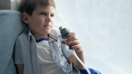 respiração : procedure of treats inflammation of airways via nebulizer in child sitting on windowsill at home close-up