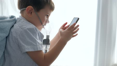respiração : Preventing asthma, child in mask from an nebulizers with gadget into hands in room close-up