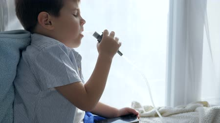 astma : Nebulizers therapy, diseased boy with smartphone in hand breathes through an inhalant for treatment close-up
