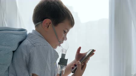 astma : medical therapy if difficulty breathing, child in mask from an nebulizers with smartphone into hands at home